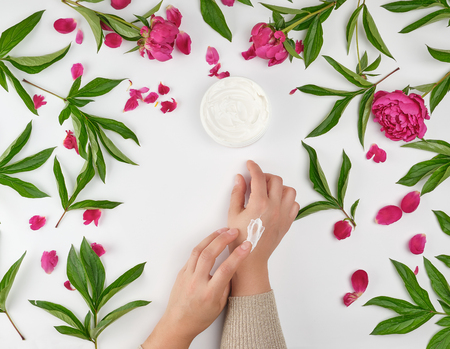 Two female hands and a jar with thick cream and burgundy flowering peonies with green leaves, top view, concept of anti-aging procedures for rejuvenating and moisturizing the skin of hands