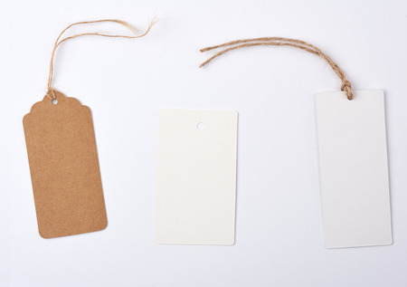 Empty paper round and rectangular brown tag on a rope, white background, sales concept