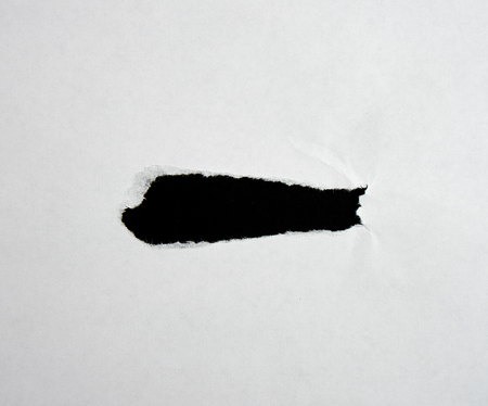 White sheet of paper with a hole, full frame, black inside