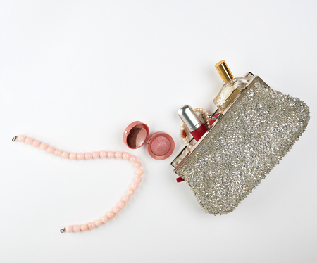open silver cosmetic bag and women's cosmetics and perfumes, red lipstick, perfume and pearl pink beads on a white background
