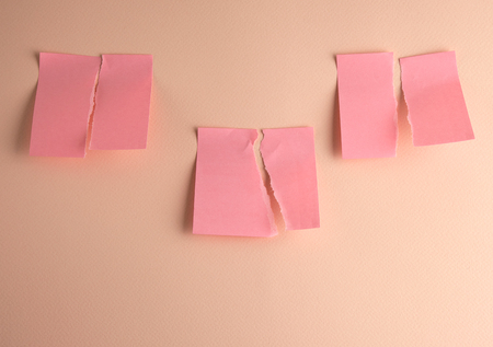 three paper pink stickers ripped in half, close up