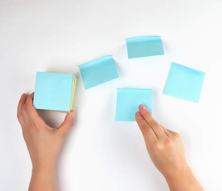 lot of empty blue stickers on a white background and two female hands, conceptual background Stock Photo