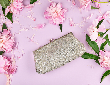 Closed silver women's handbag with sequins for cosmetics on a lilac background with blooming buds of pink peony, top view