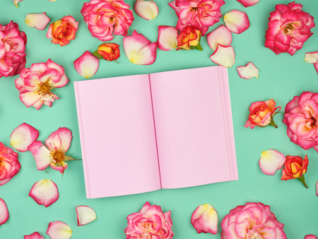 open notebook with pink blank pages on a green background and petals of a pink roses , top view