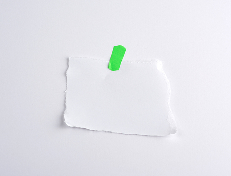 torn off white piece of paper glued to green piece label, white background