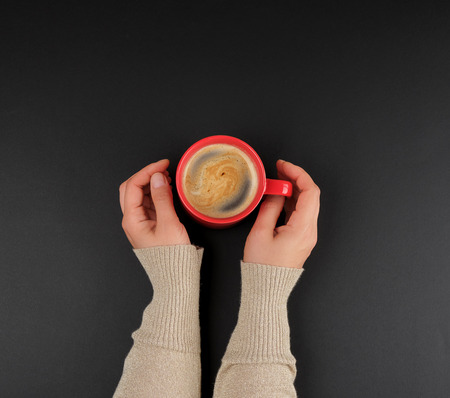 red creameric cup with black coffee in female hands , black background, top view Stockfoto