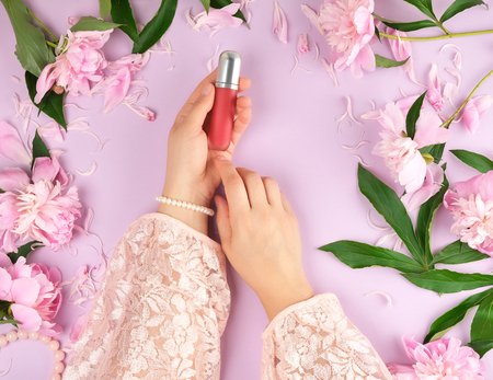 womens hands hold red lipstick, purple background with blooming pink peonies, trendy concept