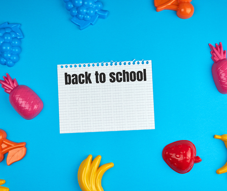 white sheet torn out of notepad on a blue background in the midst of childish toys, inscription back to school Stockfoto