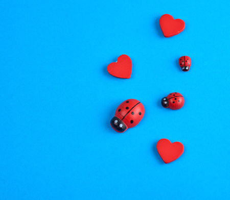 wooden decor red heart and ladybug on a blue background, close up Stockfoto