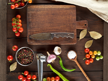 old brown empty kitchen cutting and fresh red cherry tomatoes with green chili peppers on the table, top view Stockfoto