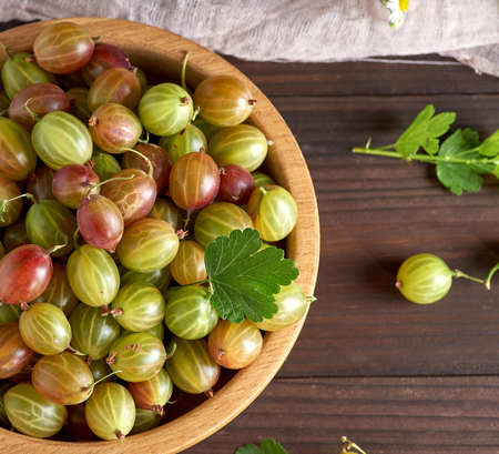 round wooden bowl with green and yellow gooseberries, brown table, top view Stockfoto