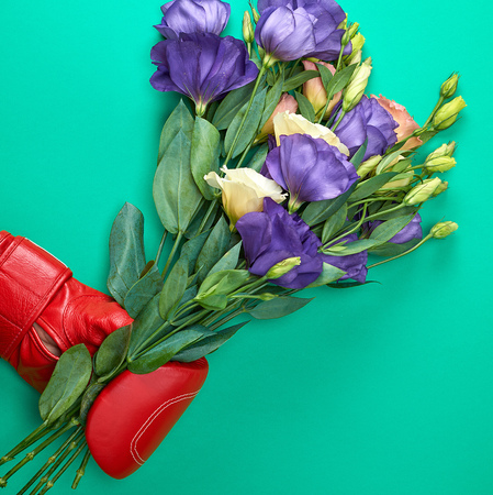 hand in a red boxing glove holding a bouquet of flowers Eustoma Lisianthus on a green background Stockfoto