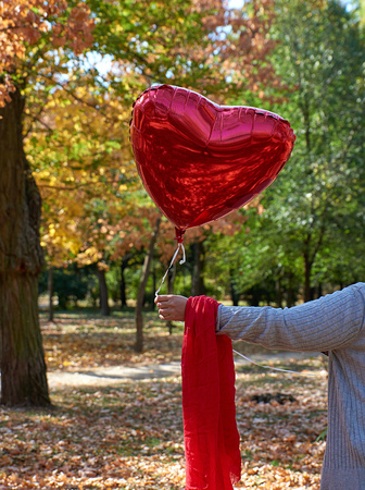 female hand holding a red balloon in the shape of a heart against the background of the autumn park