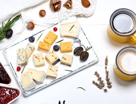different pieces of cheese on a white wooden board and two yellow cups with a coffee drink, top view