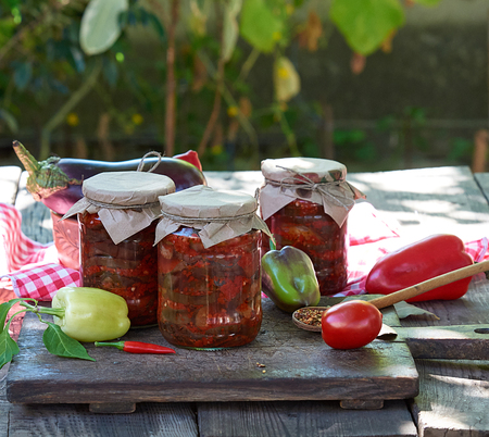 Canned eggplant slices in spicy vegetable sauce in glass jars on a wooden table Stockfoto
