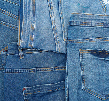 Lots of blue classic jeans stacked chaotically, back pocket, full frame