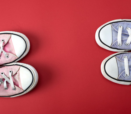 two pairs of worn classic textile pairs of shoes on a red background, top view, copy space