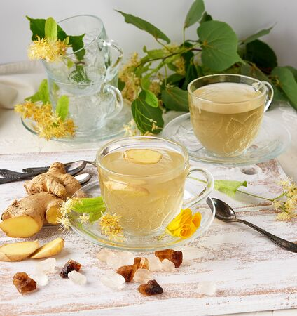 transparent cup of herbal linden tea and pieces of ginger on a white wooden board, next to pieces of sugar and twigs with green leaves