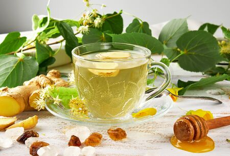 transparent cup with tea from ginger  and linden on a white wooden board, next to pieces of sugar and twigs with green leaves