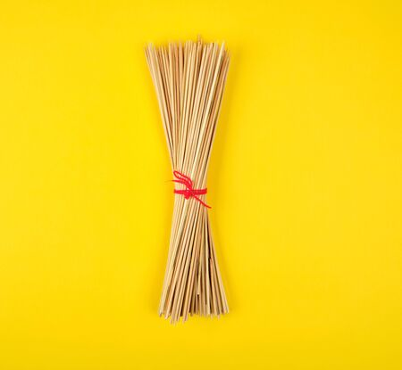 related sharp bamboo sticks barbecue on a yellow background, top view