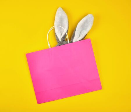 rectangular pink paper shopping bag with a white handle on a yellow background, with bunny ears sticking out of the bag, flat lay
