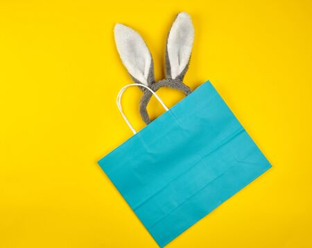 rectangular blue paper shopping bag with a white handle on a yellow background, with bunny ears sticking out of the bag, flat lay