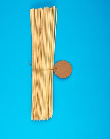 bound stack of wooden bamboo sticks for barbecue on a blue background, empty space Stock Photo - 125334781