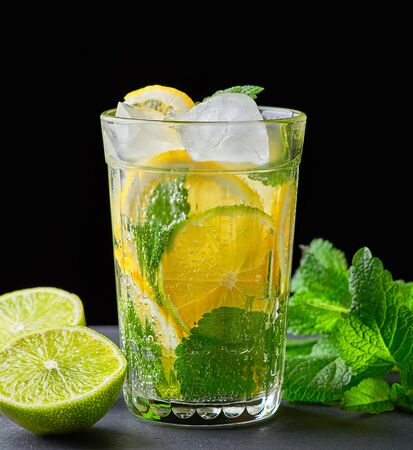 cold drink made from pieces of lemon, lime and leaves of green mint in a glass with water drops, next to ingredients for making lemonade