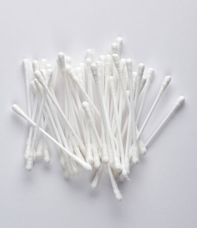 plastic sticks with white cotton for ear cleaning and other hygiene procedures on a white background Stock Photo
