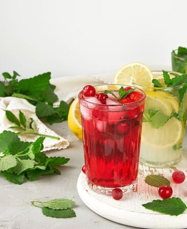 refreshing summer drink of strawberries and cranberries on a white wooden board, behind it are yellow lemons and green mint leaves