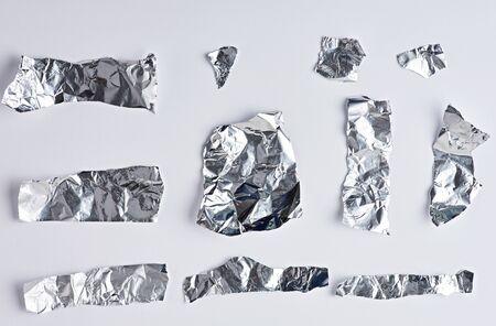 divers morceaux de feuille d'argent sur fond blanc, gros plan