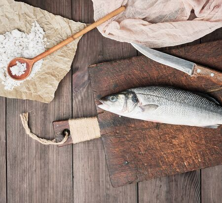 fresh whole sea bass fish and knife on brown cutting board , top view