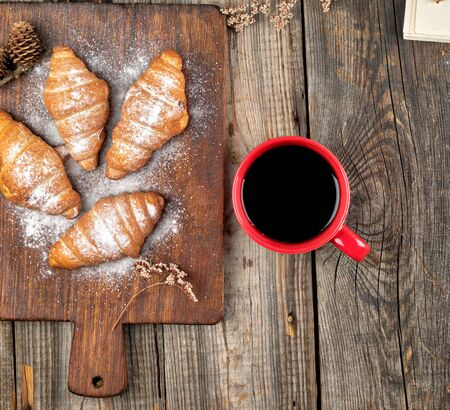 ceramic red cup with black coffee and wooden cutting board with baked croissants, baked with powdered sugar, top view Reklamní fotografie