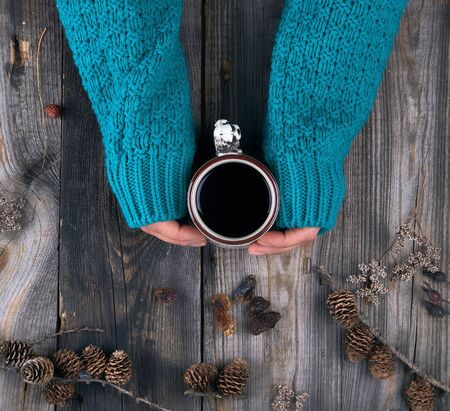 female hands in a green knitted sweater holding a ceramic mug with black coffee, gray wooden table, top view
