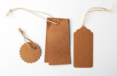 various brown paper tags with ropes on white background, business concept