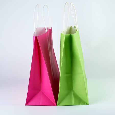 rectangular pink and green  paper shopping bags with a handle on a white  background,  close up Banco de Imagens