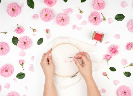 two female hands holding a round wooden hoop and a red thread with a needle, the concept of embroidery products, top view
