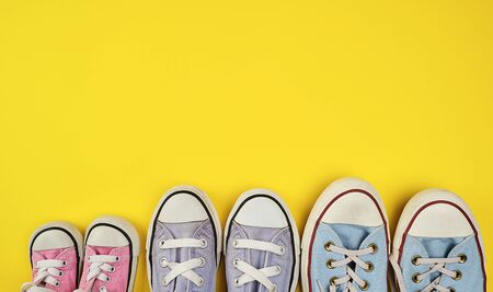lot of textile worn sneakers of different sizes on a yellow background, empty space , family concept