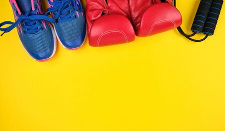 pair of blue sneakers, red leather boxing gloves and a black jump rope, yellow sports background Stock Photo