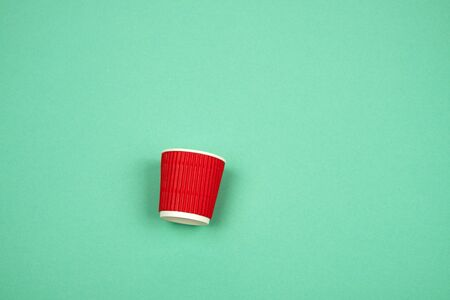 red paper cup with corrugated edges for hot drinks on a green background, copy space