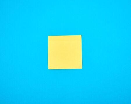 gelber leerer Papierquadrataufkleber auf blauem Hintergrund, Kopierraum