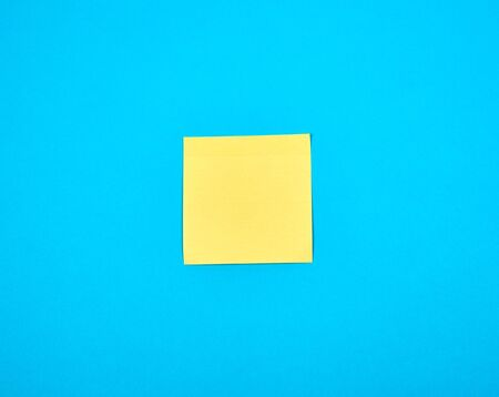 yellow empty paper square stickeron blue background, copy space