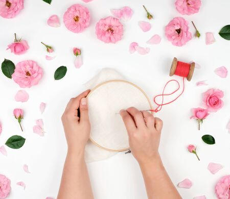 two female hands holding a round wooden hoop and a red thread with a needle, concept of embroidery products, top view