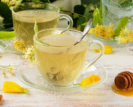 transparent cup with tea from linden on a white wooden board, close up