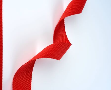 twisted red textile belt with a coarse fiber on a white background, close up