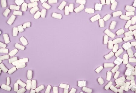 white foam filler for filling parcels during transportation on a lilac background, copy space