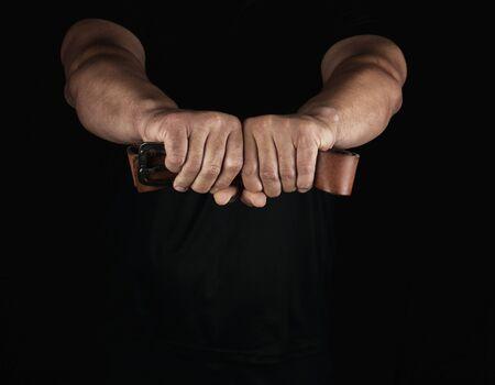 Erwachsener Mann in schwarzer Kleidung, der einen braunen Ledergürtel mit einer eisernen Schnalle hält, Konzept von Gewalt und Aggression Standard-Bild
