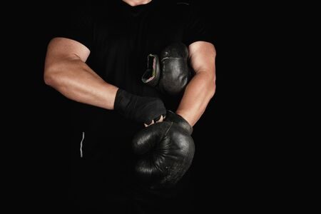 adult muscular man in black clothes puts on leather black boxing gloves on his hands before a competition, his hands are wrapped in a black sports bandage.