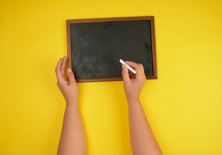 black chalk frame and two female hands with a piece of white chalk, yellow background