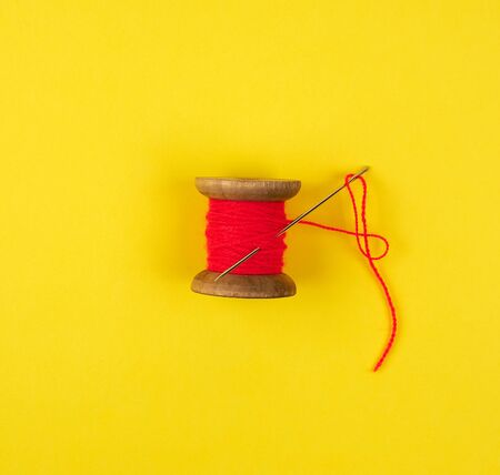 wooden reel with red wool thread and a large needle, yellow  background, copy space